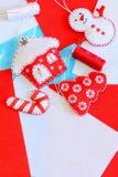 逗人喜爱的圣诞树装饰品 毛毡房子、圣诞树,棒棒糖装饰品,红色和白色螺纹,在毛毡背景的针 库存图片