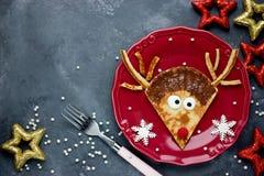 逗人喜爱的圣诞节食物想法-滑稽的驯鹿薄煎饼 免版税库存照片