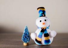 逗人喜爱的在一个帽子和一点玩具树的圣诞节白色雪人在背景中点燃 库存图片