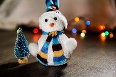 逗人喜爱的在一个帽子和一点玩具树的圣诞节白色雪人在背景中点燃 免版税图库摄影