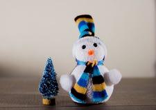 逗人喜爱的在一个帽子和一点玩具树的圣诞节白色雪人在背景中点燃 免版税库存照片