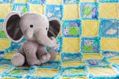 逗人喜爱的在一床五颜六色的被子的婴孩大象填充动物玩偶 免版税库存照片