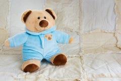 逗人喜爱的在一床白色被子的熊填充动物玩偶 免版税图库摄影