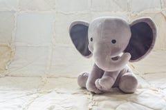 逗人喜爱的在一床白色被子的婴孩大象填充动物玩偶 库存照片