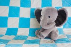 逗人喜爱的在一条蓝色方格的毯子的婴孩大象填充动物玩偶 免版税图库摄影