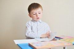 逗人喜爱的在书桌的男孩和纸画象有笔的在教室 免版税库存照片