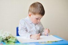 逗人喜爱的在书桌的男孩和纸画象有笔的在教室 图库摄影