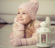 逗人喜爱的在圣诞节时间的女孩和手套画象帽子的 库存照片
