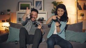 逗人喜爱的在家打电子游戏的夫妇丈夫和妻子,快乐人赢得 股票录像