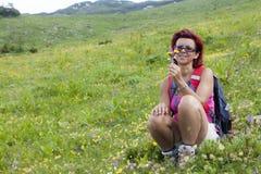 逗人喜爱的在山的妇女远足者嗅到的草本 免版税库存图片