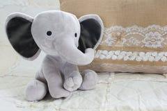 逗人喜爱的在白色被子的婴孩大象填充动物玩偶有粗麻布的 免版税库存图片