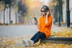 逗人喜爱的在耳机的少女听的音乐,都市样式,时髦的行家青少年坐在城市街道上的一条边路 免版税库存图片
