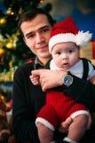 逗人喜爱的坐在圣诞树的小男孩和他的父亲 免版税库存图片