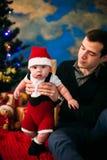 逗人喜爱的坐在圣诞树的小男孩和他的父亲 图库摄影