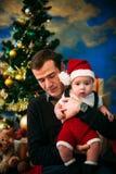 逗人喜爱的坐在圣诞树的小男孩和他的父亲 库存照片