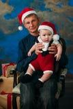 逗人喜爱的坐在圣诞树的小男孩和他的祖父 库存图片
