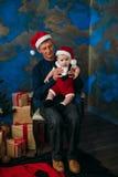 逗人喜爱的坐在圣诞树的小男孩和他的祖父 图库摄影