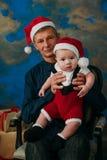 逗人喜爱的坐在圣诞树的小男孩和他的祖父 免版税库存照片