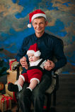 逗人喜爱的坐在圣诞树的小男孩和他的祖父 免版税库存图片