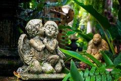 逗人喜爱的夫妇丘比特雕象在庭院里 库存照片