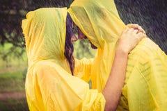 逗人喜爱的夫妇佩带的保护海角和拥抱在雨下 免版税库存图片