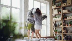 逗人喜爱的夫妇在与笑的毯子的床上跳舞跳跃和一起获得乐趣在周末早晨在好的光 股票视频