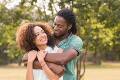 逗人喜爱的夫妇在做心脏的公园塑造 免版税图库摄影
