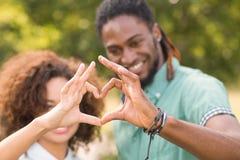 逗人喜爱的夫妇在做心脏的公园塑造 免版税库存图片