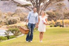逗人喜爱的夫妇在走在公园的日期 免版税库存照片