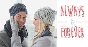 逗人喜爱的夫妇的综合图象在温暖衣物拥抱的 图库摄影