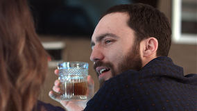 逗人喜爱的夫妇谈和喝一杯在酒吧 免版税图库摄影