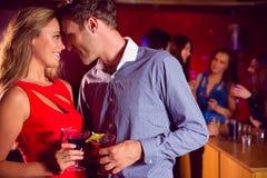 逗人喜爱的夫妇饮用的鸡尾酒一起 免版税库存照片
