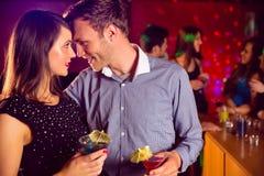 逗人喜爱的夫妇饮用的鸡尾酒一起 免版税库存图片