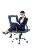 逗人喜爱的女商人坐椅子和与膝上型计算机iso一起使用 库存图片