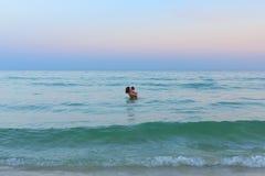 逗人喜爱的女婴和美好的母亲亲吻在海 免版税图库摄影