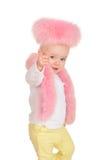 逗人喜爱的女婴在空白背景的桃红色毛皮作用穿戴了 库存照片