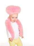 逗人喜爱的女婴在空白背景的桃红色毛皮作用穿戴了 免版税图库摄影