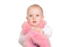 逗人喜爱的女婴在空白背景的桃红色毛皮穿戴了 库存照片