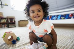 逗人喜爱的女婴获得乐趣在与玩具的游戏室 库存照片