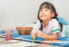 逗人喜爱的女学生享用绘颜色 库存照片