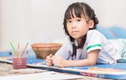 逗人喜爱的女学生享用绘颜色 免版税库存照片