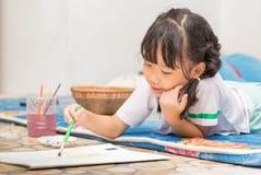 逗人喜爱的女学生享用绘颜色 图库摄影