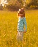 逗人喜爱的女孩一点草甸走 库存照片