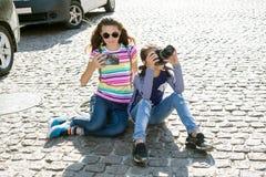 逗人喜爱的女孩为照片使用一台照相机和一个智能手机 库存照片