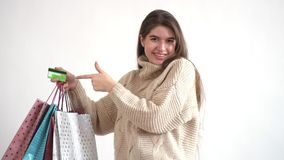 逗人喜爱的女孩举有一束的一只手购物带来和信用卡 并且他指向卡片 股票录像