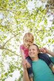逗人喜爱的女孩乘驾在她的爸爸肩膀扛在肩上 免版税库存照片