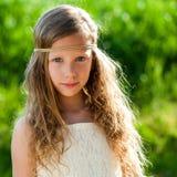 逗人喜爱的女孩佩带的丝带头饰带画象  免版税库存图片
