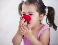 逗人喜爱的女孩佩带的小丑鼻子在家 库存图片