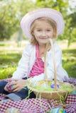 逗人喜爱的女孩佩带的帽子享用她的复活节彩蛋 库存照片