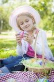 逗人喜爱的女孩佩带的帽子享用她的复活节彩蛋 免版税图库摄影